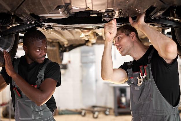 Zwei interracial verschiedene mechaniker, die auto-boden im auto-service überprüfen