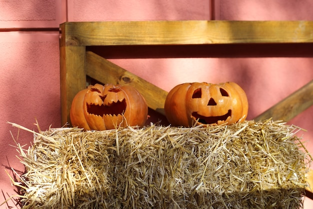 Zwei jacks o laterne auf einer strohpackung. halloween kürbisse. halloween-dekorationen im freien