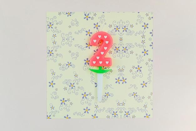 Zwei-jährige kerze auf blumenpapier des handwerks über dem farbigen hintergrund