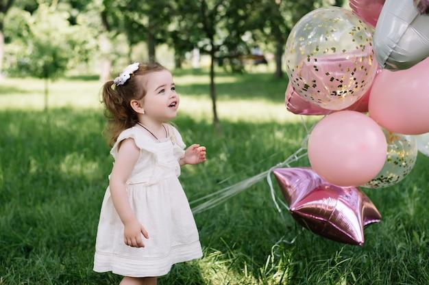 Zwei jahre altes mädchen mit ballons, die geburtstagsfeier feiern