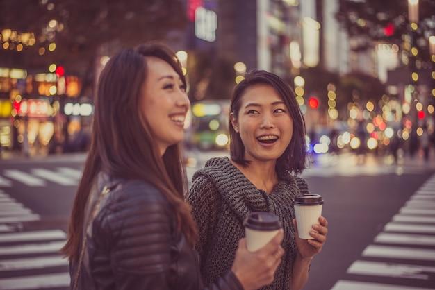 Zwei japanische frauen herum in tokio während des tages. einkaufen und spaß haben