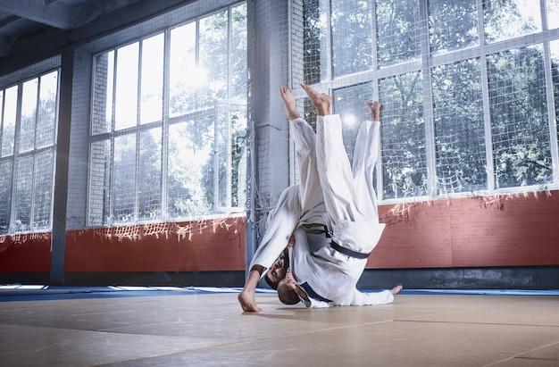 Zwei judo-kämpfer, die technische fähigkeiten beim üben von kampfkünsten in einem kampfclub zeigen. die beiden passen männer in uniform. kampf, karate, training, kunst, athlet, wettkampfkonzept