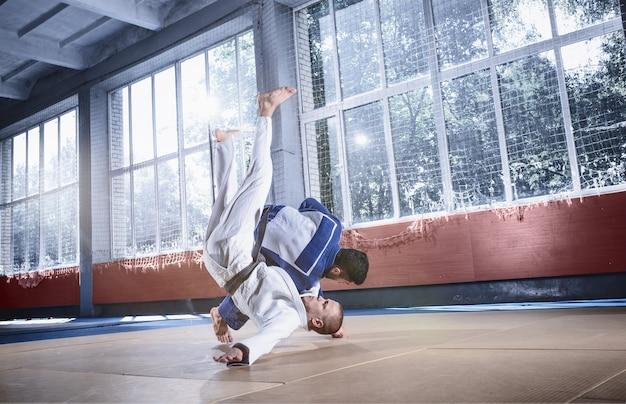 Zwei judo-kämpfer, die technische fähigkeiten beim üben von kampfkünsten in einem kampfclub zeigen
