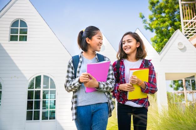 Zwei jugendliche asiatische und europäische studentenfreundinnen, die glücklich sind, zum college oder zur schule zu gehen
