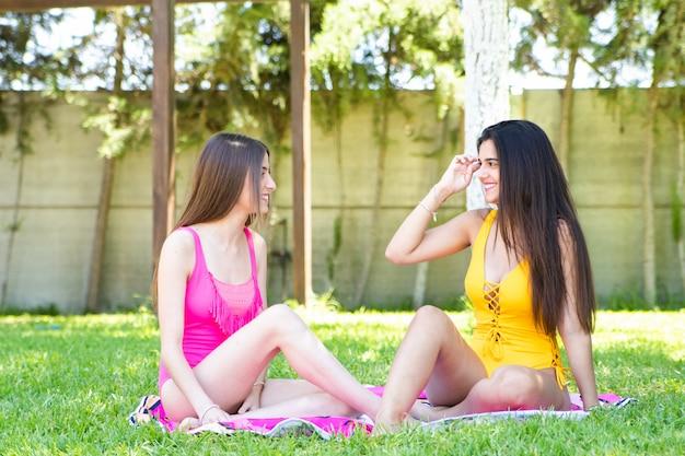 Zwei jugendliche in einem badeanzug sitzend auf dem gras im pool sprechend und lachend