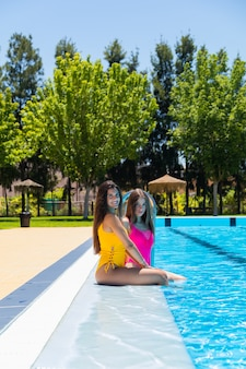Zwei jugendlichmädchen am swimmingpool