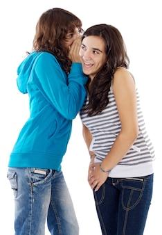 Zwei jugendlichmädchen, die ein geheimnis zum ohr flüstern