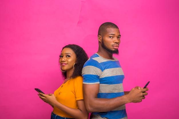 Zwei junge afrikaner, die auf rosafarbenem hintergrund isoliert sind und sich gegenseitig unterstützen, während sie ihr smartphone, telefon, handy bedienen.