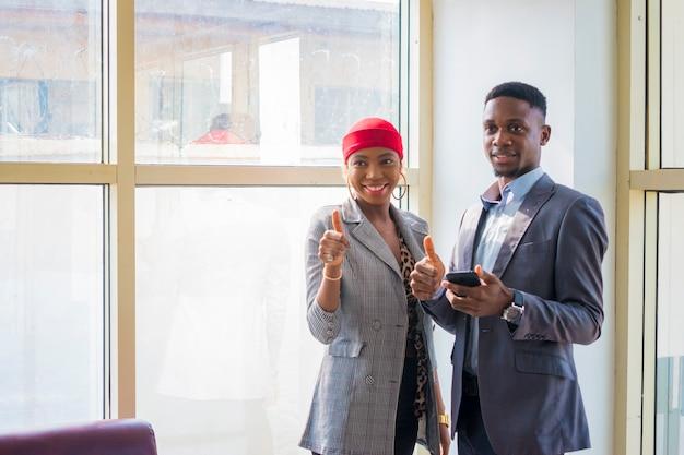 Zwei junge afrikanische geschäftspartner diskutieren über das, was sie auf ihrem handy gesehen haben und daumen hoch.