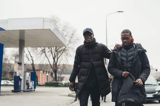 Zwei junge afrikanische männer, welche die straße kreuzen