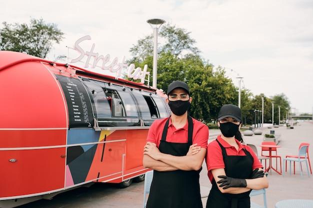 Zwei junge angestellte in uniform und schutzmasken