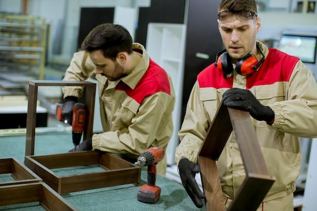 Zwei junge arbeitnehmer, die möbel in der fabrik zusammenbauen