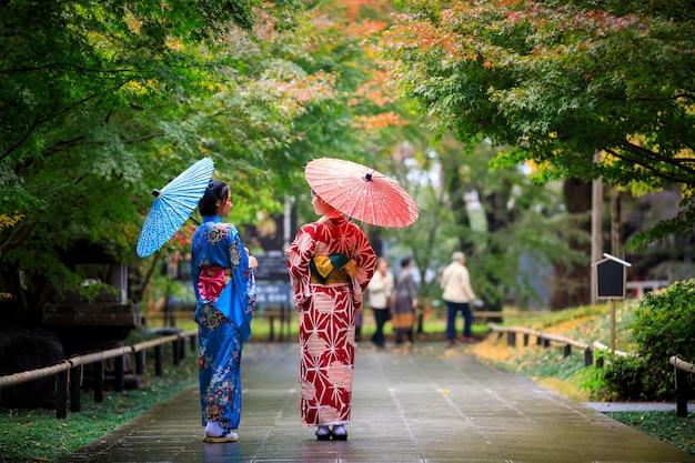 Zwei junge asiatische frau mit blauem und rotem kimono mit regenschirm an der hand, die in der herbstsaison in japan im park spazieren geht
