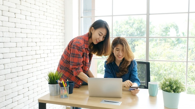 Zwei junge asiatische frauen, die kreditkarte halten und laptop-computer für den einkauf online mit glück verwenden