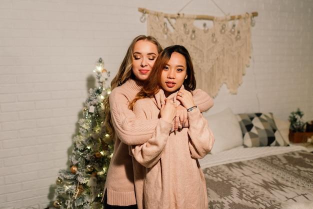 Zwei junge asiatische frauen, die mit glück in der weihnachtsfeier lächeln, lgbt paar, freunde feiern