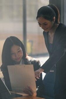 Zwei junge asiatische geschäftsfrau, die geschäftsdaten bespricht und im büro zusammenarbeitet.