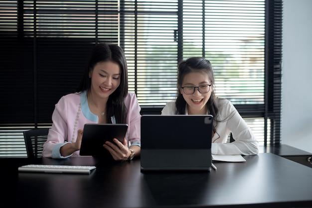 Zwei junge asiatische geschäftsfrauen diskutieren während des bürotreffens über neue geschäftsprojekte