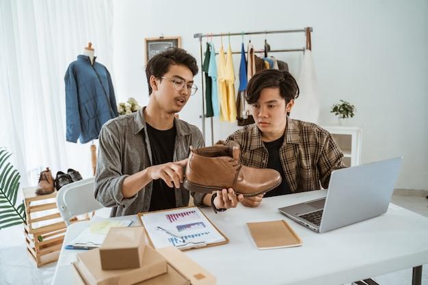 Zwei junge asiatische geschäftsleute, die über ihr produkt plaudern