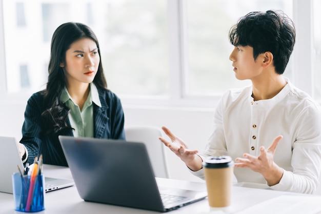 Zwei junge asiatische geschäftsleute diskutieren über das projekt zum jahresende