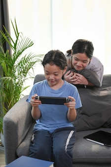 Zwei junge asiatische mädchen, die zu hause zusammen videospiele spielen.
