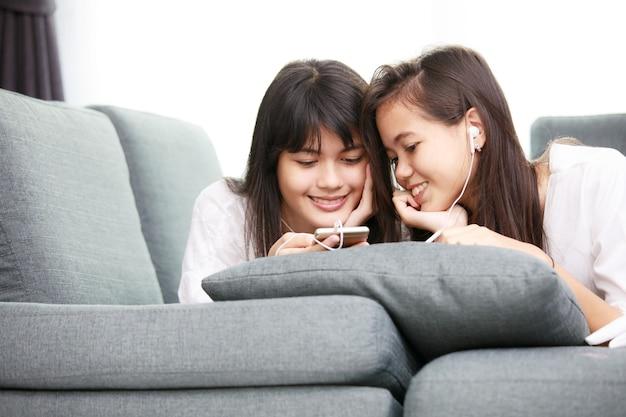 Zwei junge asiatische mädchen, die zusammen smathphone betrachten, während sie sich auf dem sofa zu hause hinlegen