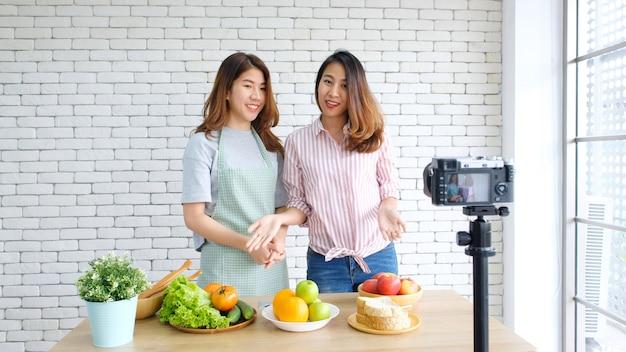 Zwei junge asiatische sprechende frauenlebensmittelblogger bei der aufnahme des videos mit glücklichem moment