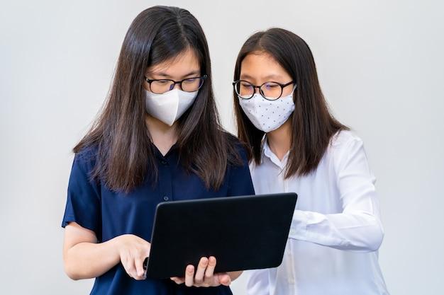 Zwei junge asiatische teenager, die masken tragen und zu eng an ihrem schulprojekt arbeiten