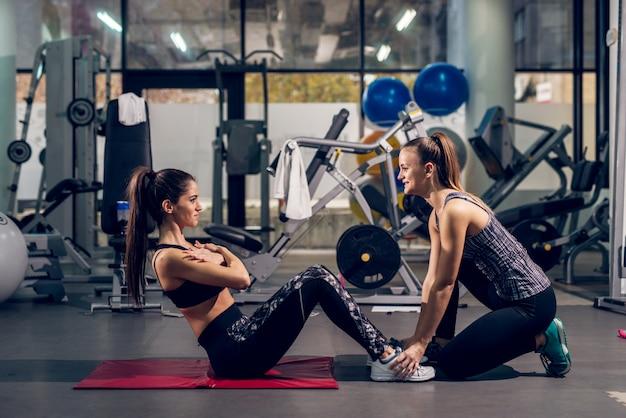 Zwei junge attraktive fröhliche sportliche aktive mädchen, die liegestütze in einem team im modernen fitnessstudio machen.