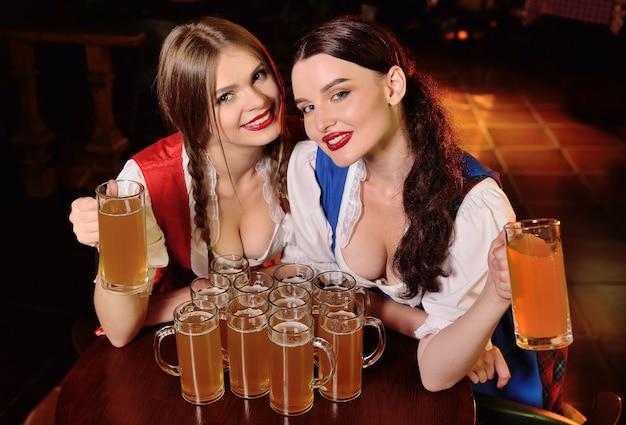 Zwei junge attraktive mädchen in den bayerischen kleidern, die an einem tisch in einem trinkenden bier der bar und in stoßenden gläsern während der feier des oktoberfestes sitzen