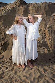 Zwei junge attraktive zwillinge mit langen haaren verbringen im sommer zeit miteinander im freien und posieren im sandsteinbruch in weißem kleid, rock, jacke
