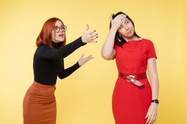 Zwei junge aufgeregte geschäftsfrau oder freundin schwören sich mit negativen emotionen. reizende frau, die mit stress und kopfschmerzen spricht, isoliert auf gelbem hintergrund