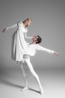 Zwei junge balletttänzer üben. attraktive tanzende darsteller in weiß