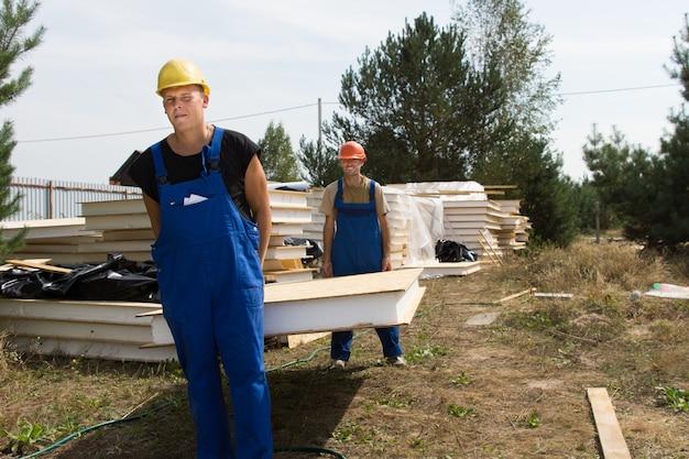 Zwei junge bauarbeiter in schutzhelmen und overalls tragen eine wanddämmplatte auf einer baustelle building