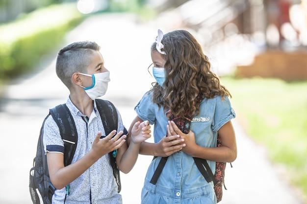 Zwei junge befreundete klassenkameraden mit gesichtsmasken unterhalten sich während der covid-19-quarantäne auf dem weg zur schule.