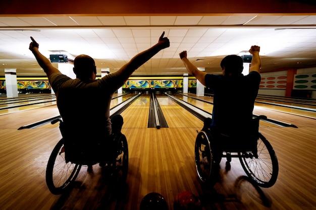 Zwei junge behinderte männer im rollstuhl spielen bowling im club