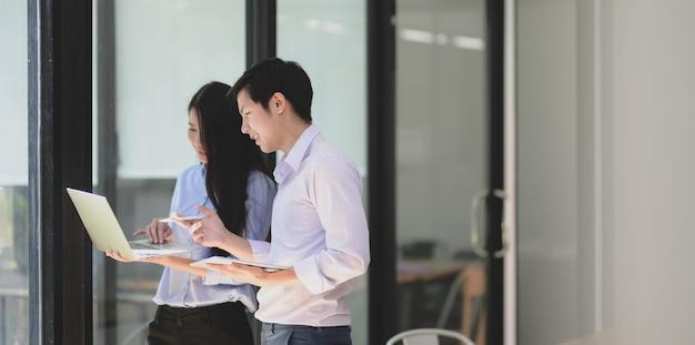 Zwei junge berufstätige geschäftspartner tauschen sich gemeinsam über das aktuelle projekt aus