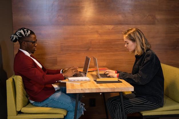 Zwei junge beschäftigte studenten in freizeitkleidung sitzen am tisch im café, während sie auf laptops tippen und hausaufgaben machen