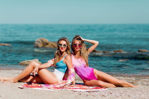 Zwei junge beste freunde sitzen am tropischen strand und genießen sommerferien.