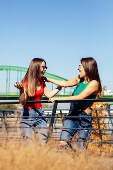 Zwei junge beste freundinnen, die an der alten brücke stehen