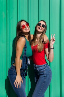 Zwei junge beste freundinnen, die an der grünen wand stehen