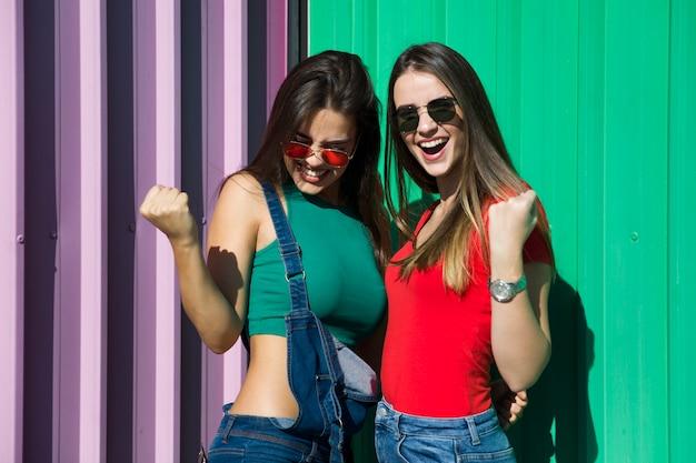 Zwei junge beste freundinnen, die an der wand stehen