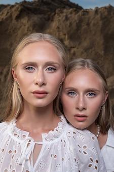 Zwei junge blonde hübsche zwillinge im sandsteinbruch in eleganten weißen kleidern.