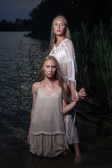 Zwei junge blonde zwillingsschwestern, die in der sommernacht in hellen kleidern im wasser des sees aufwerfen.