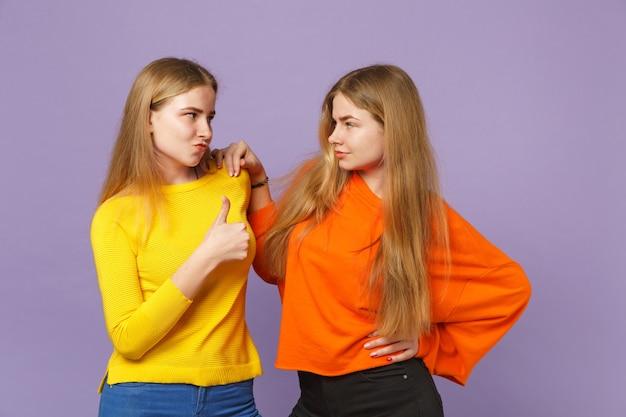 Zwei junge blonde zwillingsschwestern mädchen in lebhaften bunten kleidern, die sich gegenseitig ansehen und den daumen einzeln auf pastellvioletter blauer wand zeigen. menschen-familien-lifestyle-konzept.