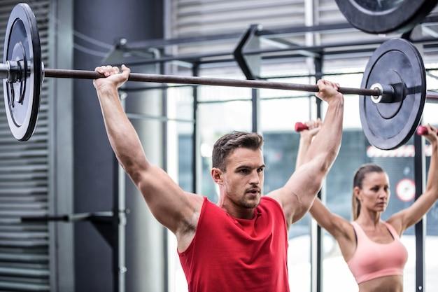 Zwei junge bodybuilder, die gewichtheben tun