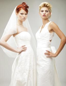 Zwei junge bräute, die im studio aufwerfen