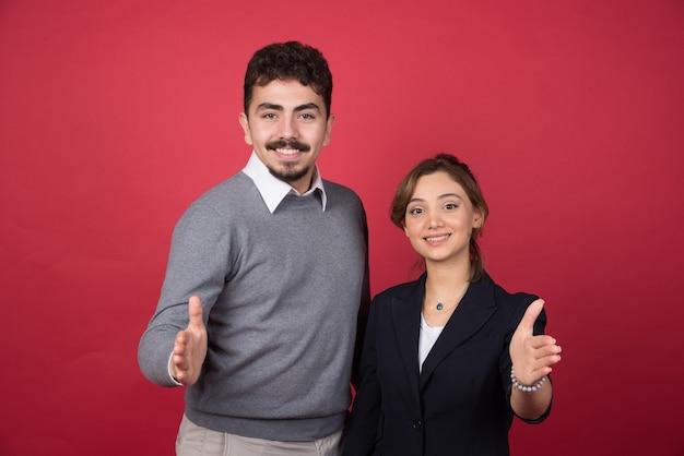 Zwei junge büroangestellte bieten ihre hände zum händedruck an