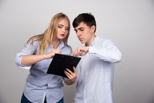 Zwei junge bürokollegen diskutieren ein projekt an einer grauen wand.