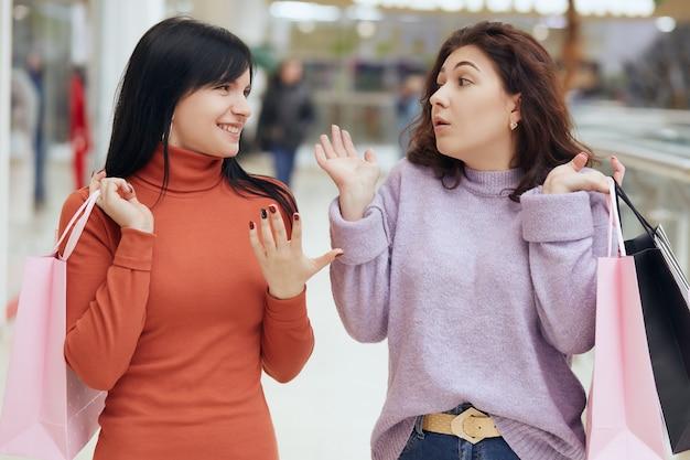 Zwei junge dame, die freizeitkleidung trägt und dunkles haar hat, im einkaufszentrum spaziert und klatscht