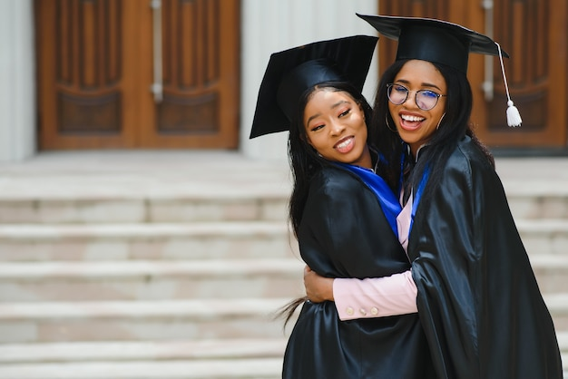 Zwei junge damen in abschlusskostümen posieren vor der kamera auf dem universitätscampus, halten diplome, lachen und umarmen, haben einen glücklichen abschlusstag, nahaufnahmeporträt